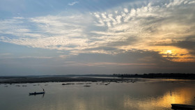 Free photo of Boat at River Under Scattered Clouds in Sky at Sunset